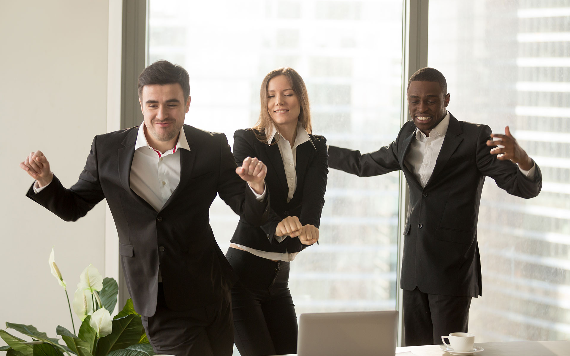 Coworkers in suits dance in conference room