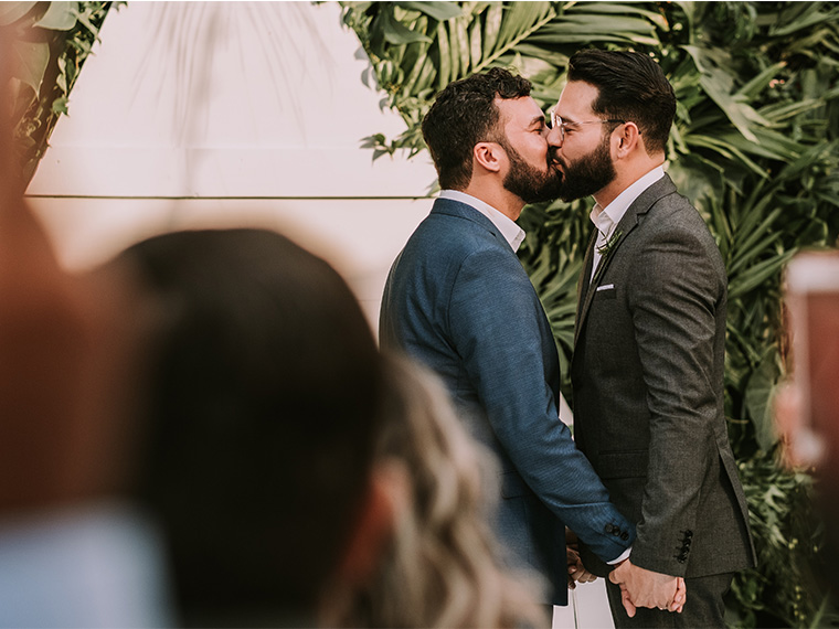 two men in a wedding kissing