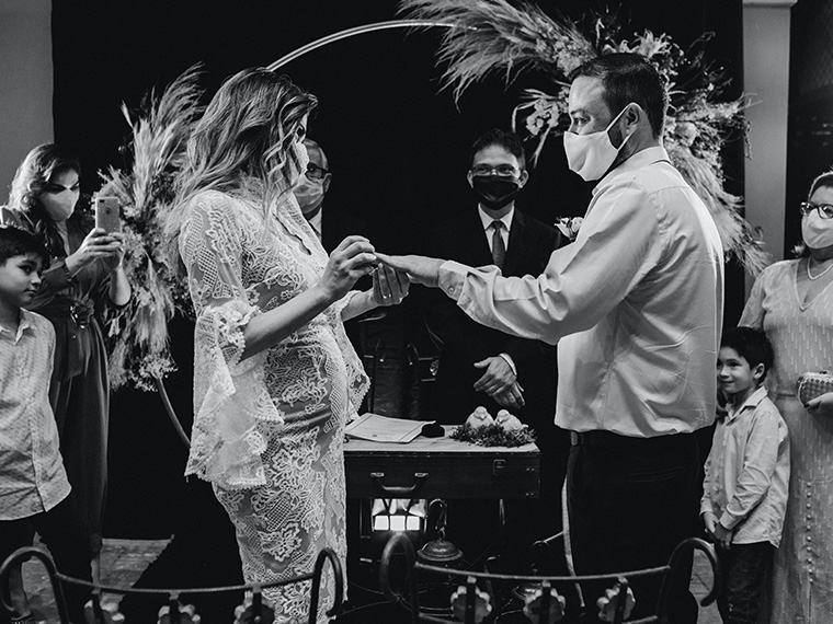 Wedding couple exchanging rings wearing masks
